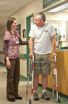 nurse assisting patient walking down hallway with walker